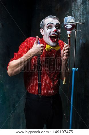 The scary clown and drip with blood on dack. Halloween concept of horror and murderer