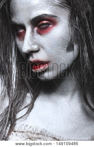 Girl in the form of zombies, Halloween corpse with blood on his lips. Image for a horror film. Photos shot in studio