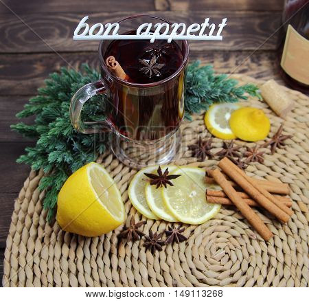 mulled wine with a lemon, cinnamon, an anisetree and a juniper and an inscription bon appetit