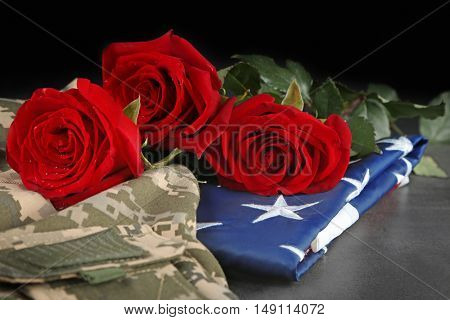 Red roses on American flag with military uniform, closeup