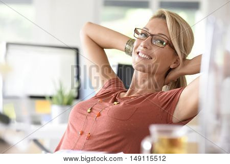 Portrait of beautiful middle-aged woman relaxing in office