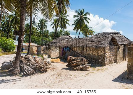 houses with thatch roofs and bundles of firewood on african beach with palms, Zanzibar