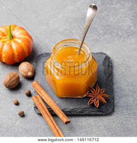 Pumpkin confiture, jam sauce with spices on stone table Top view