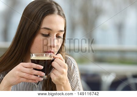 Portrait of a sad woman holding a coffee cup thinking and looking down sitting in a restaurant in a rainy day