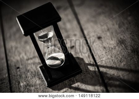 Close-up Hourglass on wood background.