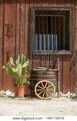 Western style wall, window of hut with barrel, wheel, cactus