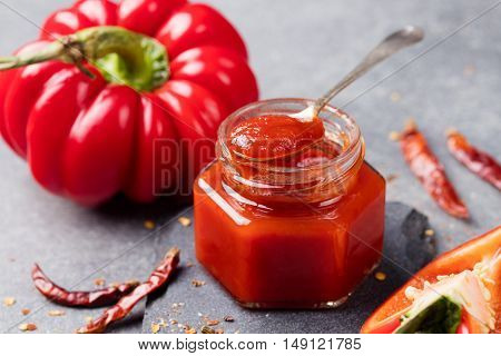 Tomato and chili sauce, jam confiture in a glass jar on a grey stone background