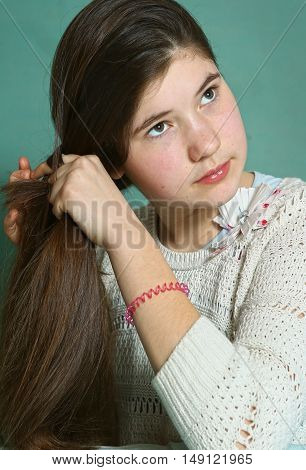 teen pretty girl with long stright thick brown hair make pony tail close up photo