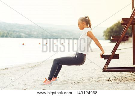 Young woman workout by the river on beach