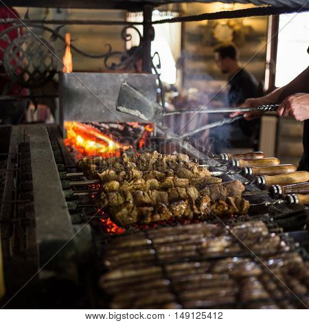 Preparing grilled skewed meat on bbq in restaurant.