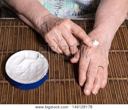 Old Woman Applying Hand Cream