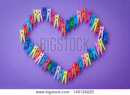 Little colorful clothes pins on a purple background