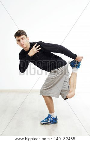 Hip hop dancer performing isolated over white background. Hip hop performer is standing in hip hop pose.