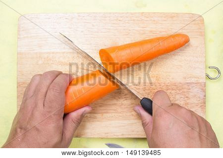 Chef cutting carrot on a wooden board cooking porkchop steak concept