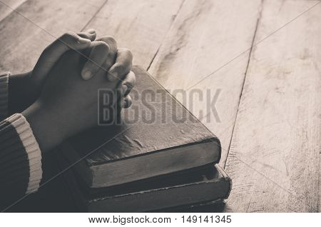 bible book bright christian christianity dark dim finger god hand holding holy home human knowledge learning light male man people person pray prayer read religion religious silence sitting spiritual spirituality study studying table text wood