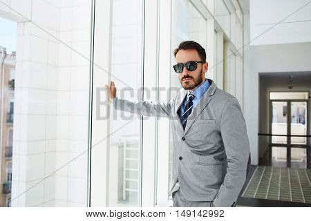 Rich businessman dressed in luxury suit is standing in his real estate company. Young male economist is posing for camera during work break.Skilled entrepreneur is waiting client in hallway enterprise