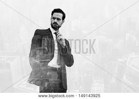 Double exposure with cityscape of business man holding glasses near mouth and looking on something with angry face. Thoughtful male entrepreneur standing with hand in pocket black and white effect
