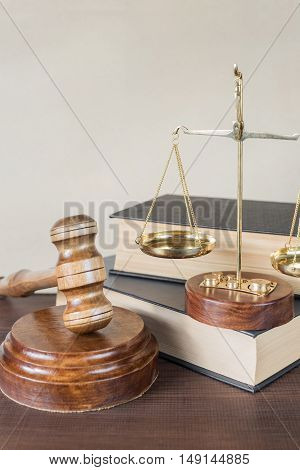 Symbols of law: wood gavel soundblock scales and two thick old books