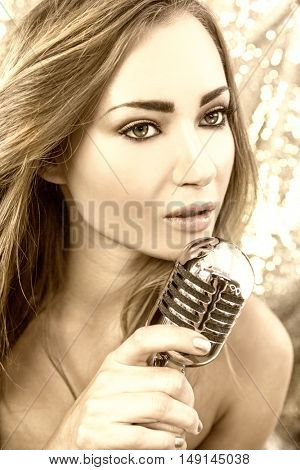 Golden toned beautiful female woman singer singing into a vintage microphone in a night club