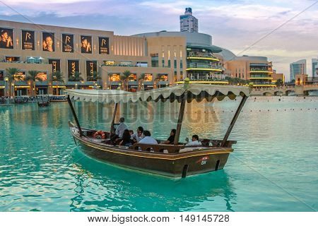 Dubai, United Arab Emirates - May 1, 2013: wooden boat in lake of Dubai fountain show area near Dubai Mall and Burj Khalifa. On the background, the Souk Al Bahar at twilight.