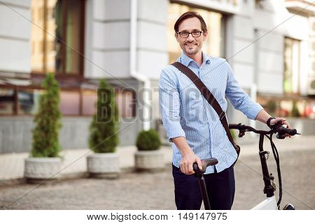 Happy ride. Handsome bespectacled man smiling and keeping bike while standing in the street.