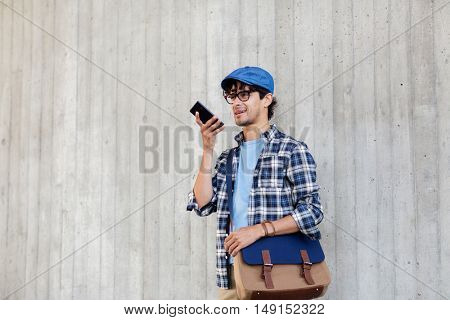 leisure, technology, communication and people concept - smiling hipster man with shoulder bag using voice command recorder or calling on smartphone at street wall poster