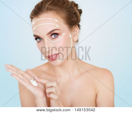 beauty, people, anti-age and cosmetics concept - happy young woman with moisturizing cream on hand and face lifting arrows over blue background