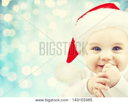 christmas, babyhood, childhood and people concept - happy baby in santa hat over blue holidays lights background