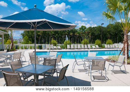 Blue umbrella on an empty pool deck on a sunny day