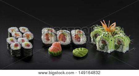 Mix colorful sushi. Uramaki and Hosomaki sushi rolls over black background