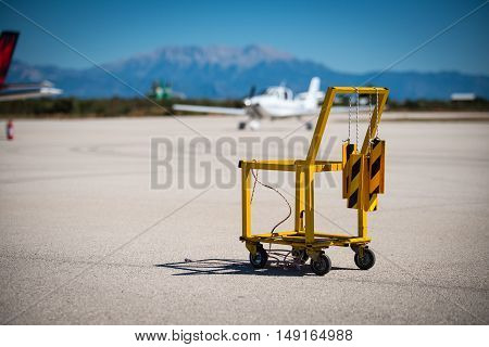 A yellow aircraft chocks and fire extinguisher carrier on a small airport. Aircraft chocks are hanging on the carriers handle. Small aircraft and scenic view on the background.