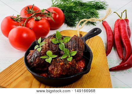 Meatballs with chili pepper and tomato served in cast iron skillet. Grilled spicy meatloaf. Barbecue meatballs.