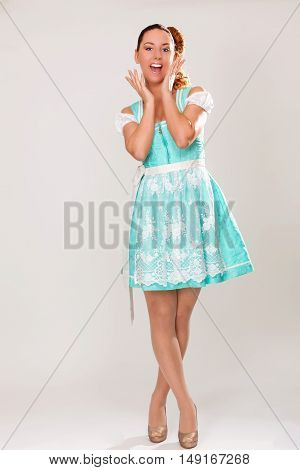 Bavarian girl in dirndl holds to call her hands to her mouth