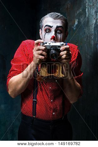 The scary clown and a camera on dack. Halloween concept of horror and murderer