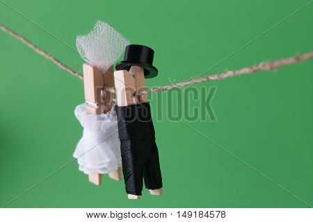 Clothespin characters on green background. Bride in white dress and groom character man suit hat. Love concept photo. Macro view, shallow depth of field
