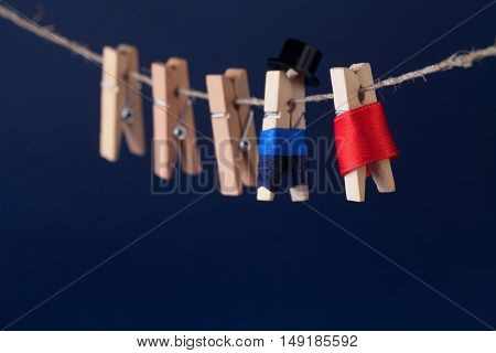 Creative design clothespin characters man in suit, woman red dress hanging on rope. Creative concept with clothesline and wooden clothespins on dark blue background. Macro view
