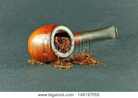 Tobacco pipe with tobaco isolated on gray background.