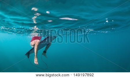 Fit active girl in bikini. Surfer on surf board wait for ocean wave. Woman feet and surfboard underwater photo. People in water sport adventure camp. Swimming extreme surfing on summer beach holiday