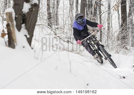 Mountainbiker riding on white snow in winter