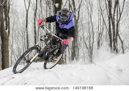 Mountainbiker riding on white snow in winter