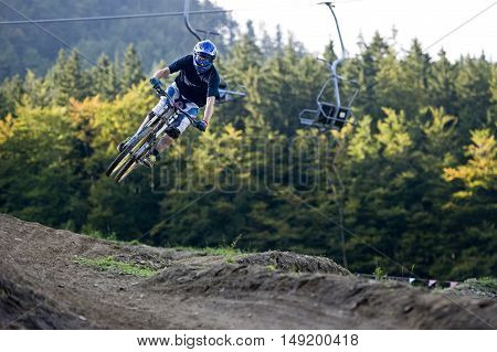Extreme mountainbiker jumps over natural mountain path