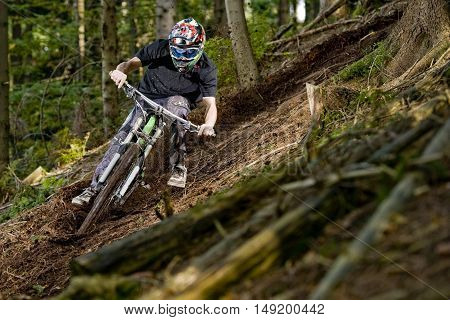 Mountainbiker rides on path in dark forest