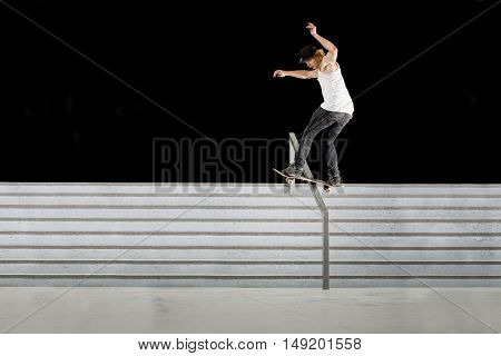 Boy doing skateboard trick boardslide on rail