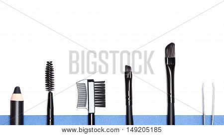 Accessories for care of the brows: eyebrow pencil, spooly brush, brow comb / brush combo, different sized angle brushes, stainless steel tweezers on white and blue background. Eyebrow grooming tools