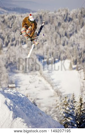Boy doing trick on skis in winter park