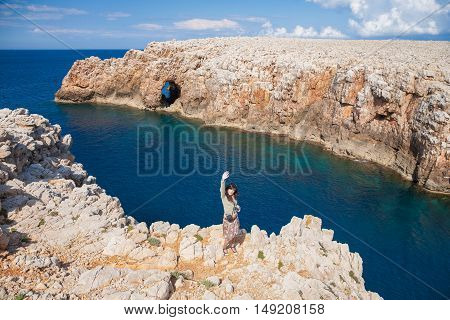 Woman Greeting On Cliff Above Sea Minorca Coast
