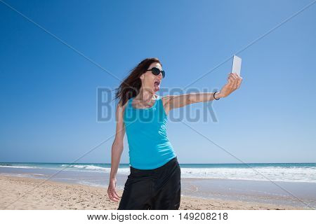 portrait of brunette woman with black sunglasses and blue cyan shirt teasing sticking out tongue making selfie with mobile phone smartphone at beach with sea behind