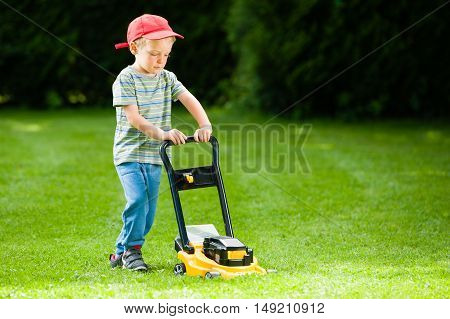 Cute boy mows lawn by yellow lawn mower