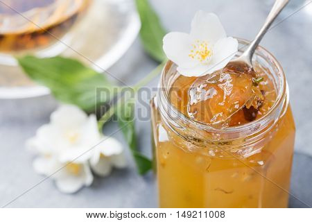 Jasmine flower confiture, jam with fresh jasmine flowers Grey stone slate background