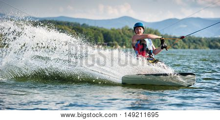 Wakeboarder surfing across a lake on sunny day